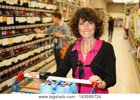 Happy Woman Shopping In The Supermarket, Wine Shelves