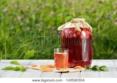 Homemade cherry preserved canned compote in glass with cookies on white wooden table in garden. Freesh fruit drink
