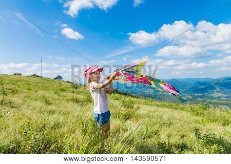 4-5 years girl holding a kite against the backdrop of beautiful mountains and green landscapes