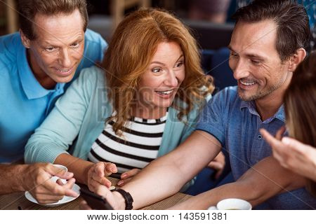 Look here. Close up of delighted and smiling friends using smartphone together and having fun