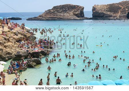 Comino Island, Malta - 03 August 2016: Tourists at the Blue Lagoon. The most famous and crowded beach in Malta with crystal clear waters.