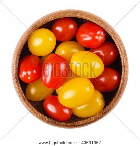 Cocktail tomatoes in a wooden bowl on white background. Yellow and red ripe fruits of Solanum lycopersicum, a berry type fruit, but are considered culinary vegetables. Edible, raw, organic food. Macro