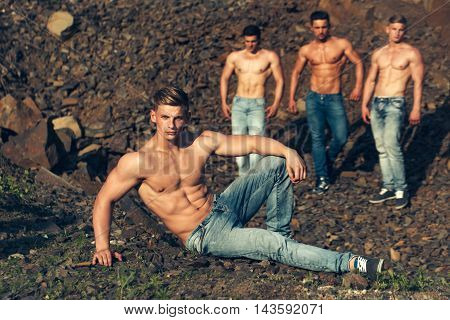 four handsome young macho men with muscular sexy body and six packs on torso in jeans sunny day outdoor on stony natural background