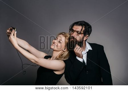 Elegant couple of young blond woman in black dress listens to music in smartphone with earphones and handsome bearded hipster man in glasses suit make selfie together on grey wall
