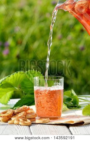 Homemade strawberry compote pouring in glass from decanter with pretzels on white wooden table in garden. Freesh fruit drink
