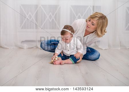 Young mother spending time at home with her little 9 month daughter. Mom and daughter dressed in white shirt and jeans