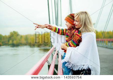 young mother and her son outdoor on the bridge