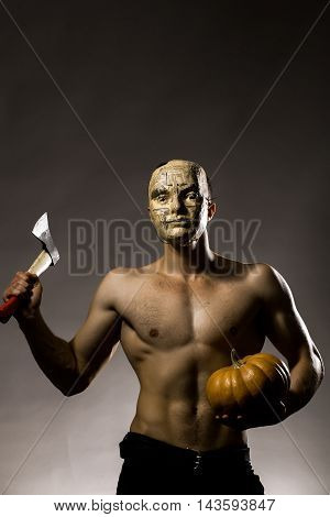 Young handsome man in mask of newspaper with muscular body bare chest and torso posing in studio holding yellow halloween pumpkin and axe on grey background
