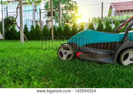 lawn mower in the garden at sunset