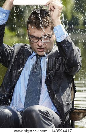 Crazy businessman in suit pouring out water from computer