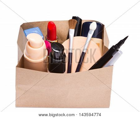 Makeup products buying theme. Paper shopping bag full of various makeup cosmetics and accessories on white background