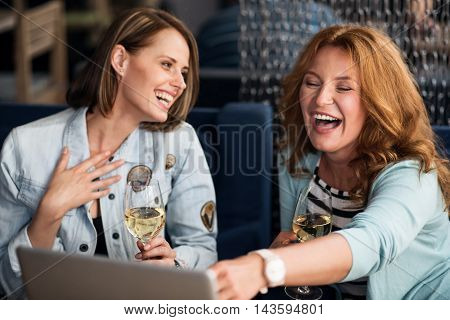 Real friends. Two positive and content women using laptop and drinking champagne