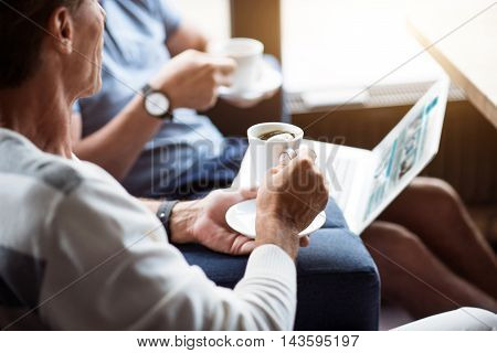 Working time. Cropped picture of two men drinking coffee and holding laptop