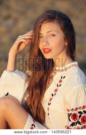 Slav teen girl portrait. Happy woman sitting on yellow meadow in national ukrainian clothing.
