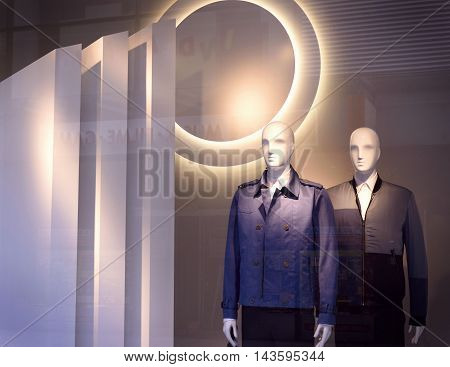 Male plastic mannequins behind a store window.
