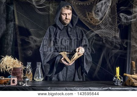 Halloween. The Medieval Alchemist Reading A Book At The Table In His Laboratory Smoke In The Backgro