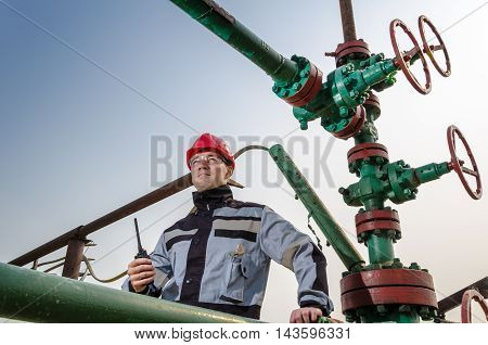 Oilfield worker near wellhead valve wearing red helmet and work clothes talking on the radio. Oil and gas concept.