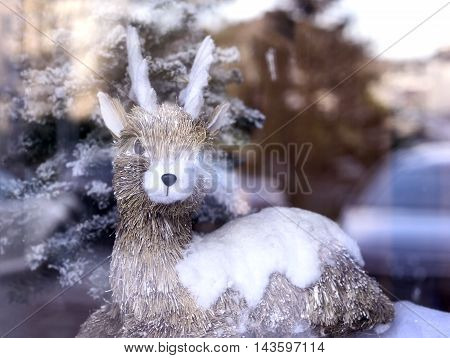 Rendeer figure behind a shop window, christmas decoration.