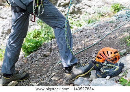 Climber man belaying with climbing gear equipment