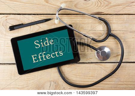 Side Effects - Workplace of a doctor. Tablet, medical stethoscope, black pen on wooden desk background. Top view.