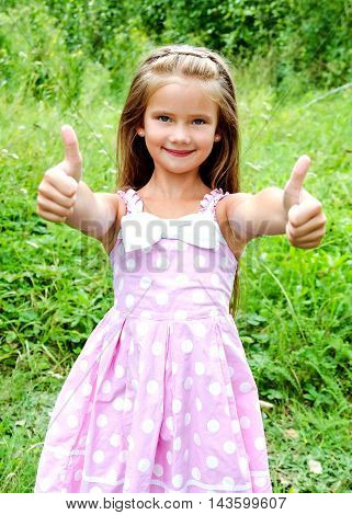 Adorable smiling little girl in with two fingers up outdoor