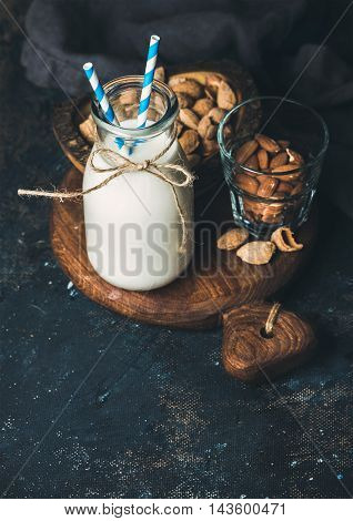 Fresh almond milk in glass bottle with almonds for healthy, raw and vegan diet on rustic wooden board over dark grunge plywood background. Selective focus, copy space, vertical composition