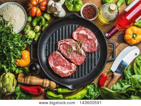 Ingredients for cooking healthy meat dinner. Raw uncooked beef steaks in cast iron grilling pan with vegetables, rice, herbs, spices and rose wine bottle over wooden background, top view