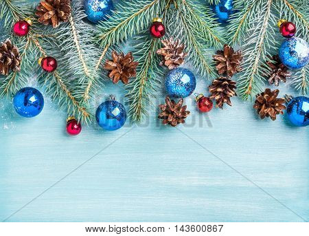 New Year or Christmas background: fir branches, colorful glass balls, cones over blue painted wooden backdrop, top view, copy space