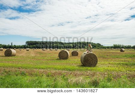 Young blond lady sitting on haystack on sunny summer day, Badasconytomaj, Hungary