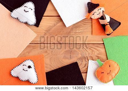 Halloween fun felt crafts. Handmade little witch with broom, pumpkin-head, two ghosts. Halloween ornaments, colored felt sheets on wooden background with copy space for text. October background