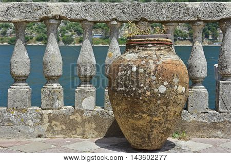 An old terracotta vase in font of a balustrade wall on Our Lady of the Rock island in Kotor Bay Montenegro. The island was artificially created by locals using rocks.