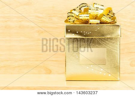 Golden Present Box With Big Bow On Wooden Table And Wood Wall,mock Up Leave Space In Middle Box To A