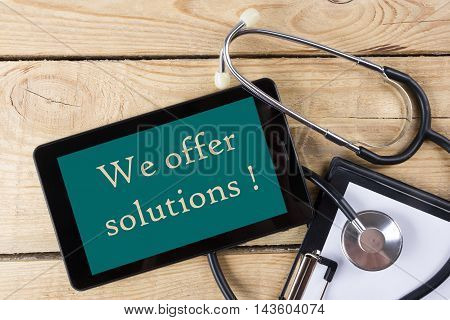 We offer solutions  - Workplace of a doctor. Tablet, stethoscope, clipboard on wooden desk background. Top view.