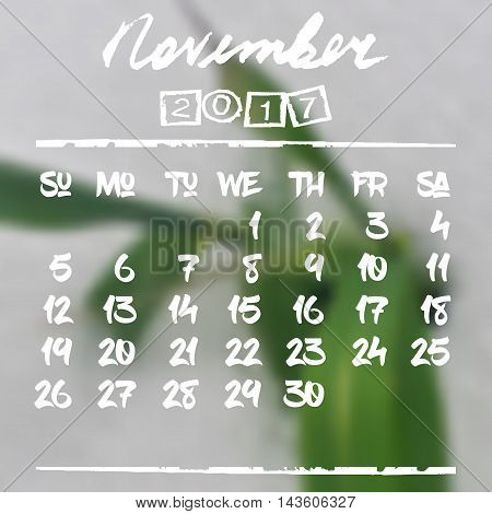Calendar design grid in hand written style with white lettering and dates of autumn month November 2017 on natural blurred background. Blurry green leaf in snow. Vector illustration