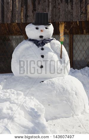 big snowman with broom and hat near fence