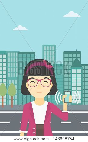 An asian woman holding ringing mobile phone on a city background. Woman answering a phone call. Woman with ringing phone in hand. Vector flat design illustration. Vertical layout.