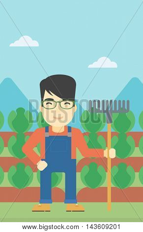 An asian friendly farmer holding a rake. Farmer standing on the background of cabbage field. Vector flat design illustration. Vertical layout.