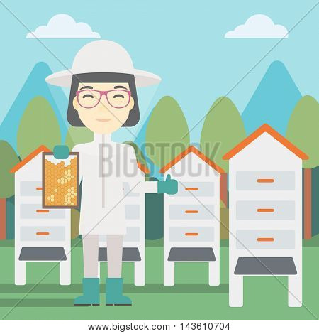 An asian female farmer wearing protective suit. Bee-keeper holding a framework in hand and showing thumb up on the background of apiary. Vector flat design illustration. Square layout.