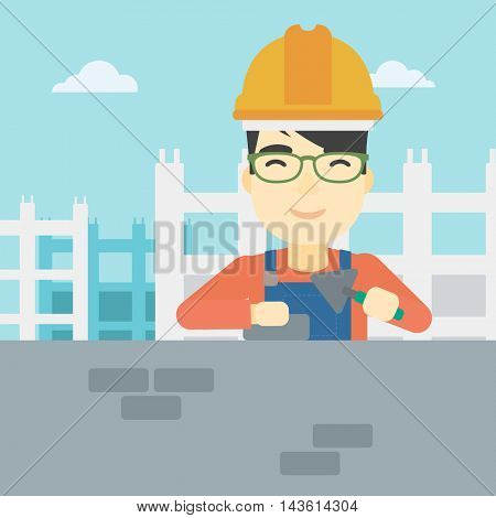 A n asian bricklayer in uniform and hard hat. Bricklayer working with a spatula and a brick in hands on construction site. Vector flat design illustration. Square layout.