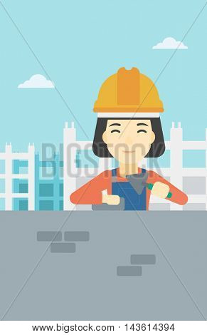 A female bricklayer in uniform and hard hat. Female bricklayer working with a spatula and a brick in hands on construction site. Vector flat design illustration. Vertical layout.