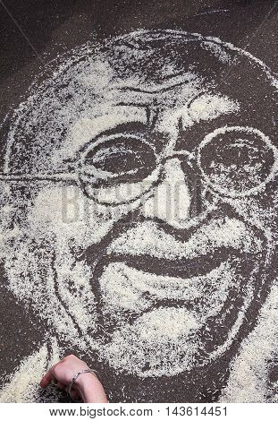 Moscow Russia - August 14 2016: Independence Day of India Celebration. Portrait of Mahatma Gandhi with rice on the asphalt.