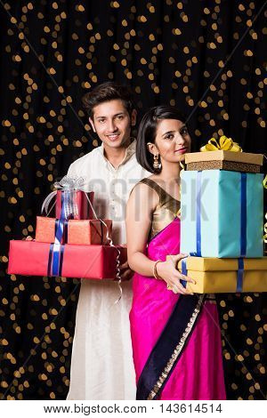 indian Couple with gift boxes in diwali festival over black background having bokeh of lighting series