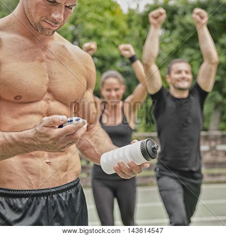 Muscular fitness instructor measuring time with stopwatch group of people exercising in the background