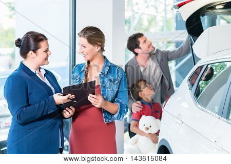 Family buying new car in auto dealer showroom, the sales lady shows the price list