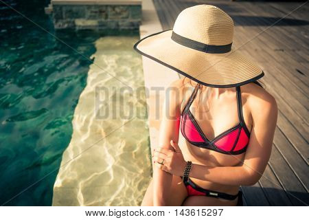 Woman in summer vacation wearing straw, hat, sunglasses and bikini, sitting at swimming pool edge