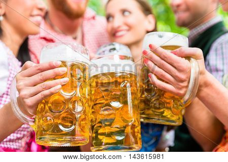 Five friends, men and women, having fun in beer garden clinking glasses with beer