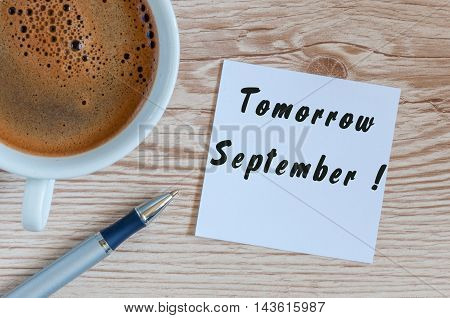 September tomorrow word wrote on white paper at wooden background with cup of morning coffee. Back to school time
