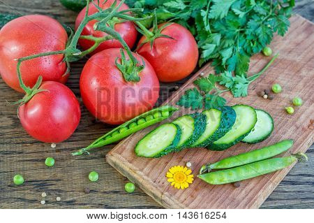 Cluster of ripe red tomatoes with water drops, sliced cucumber on wooden cutting board, bunch of parsley, green peas and peppercorn on the table, fresh vegetables, salad ingredients