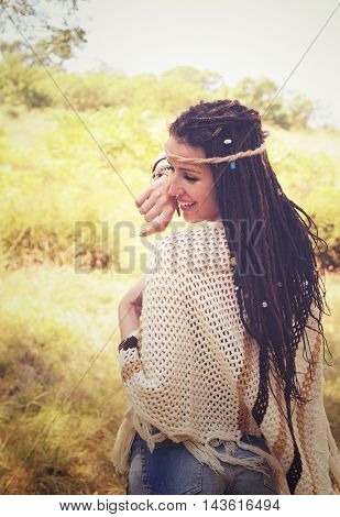 Joyful boho style girl portrait, dressed in knitted poncho and headband have a fun against sunny autumn park, vintage colors