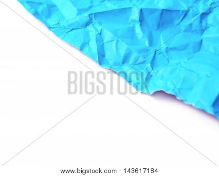 Fragment of a crumpled origami paper sheet isolated over the white background, close-up crop composition as a copyspace backdrop with a shallow depth of field